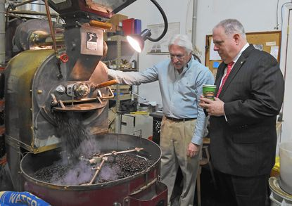 Gov. Larry Hogan, right, observes the coffee roasting process with Baltmore Coffee & Tea Factory partner Stanley Constantine during a tour.