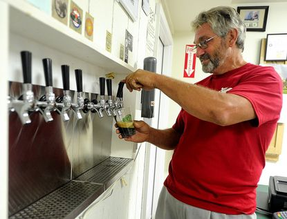 Owner Henry Ruhlman pours a cup of milk stout at Ruhlman's Brewery in Hampstead Sept. 7.