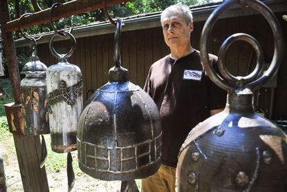 Metal sculptor Ed Kidera shows off some of the bells he has created.