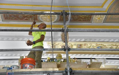 Walter Zylinski, a decorative painter with EverGreene Architectural Arts, works on the ceiling of the room that will be the Teen Room at the central Enoch Pratt Free Library.