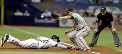 Tampa Bay Rays' Steven Souza Jr. (20) dives back to first base ahead of the throw to Orioles first baseman Chris Davis (19) on a pickoff attempt during the first inning Wednesday, April 8, 2015, in St. Petersburg, Fla.