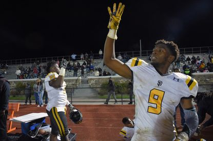 St. Frances' B'Ahmed Miller (20) and Eyabi Anoma (9) thrust four fingers skyward to honor wide receiver Tyree Henry, who was recuperating in a local hospital, following their win over the McDonogh Eagles on Oct. 14, 2016. The Panthers grounded the Eagles, 34-20.