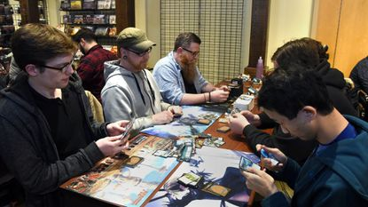 """Anton Stallick of Columbia, clockwise from left, Shane C of Highland, Robert Brennan of Columbia and Eric Kan of Wheaton play """"Magic The Gathering"""" at the Gritty Goblin Games store in Maple Lawn."""