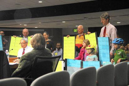 Families stand around Jack Guarneri, of Bicycling Advocates of Howard County, to share their support of the Bikeway proposal during Howard County Executive Allan Kittleman's first citizens' budget hearing on Dec. 14.