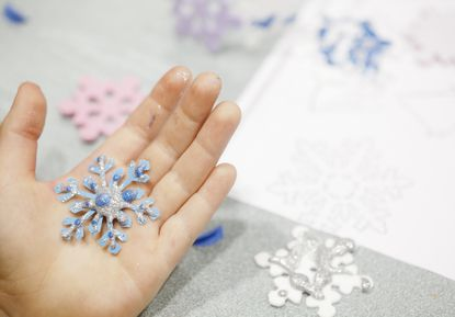 Adam Malinowski, a second grader at Carney Elementary School, holds a tiny snowflake that he decorated for the students at Sandy Hook Elementary School, the location of the school shooting last month in Connecticut. Students from Parkville and Towson schools gathered at Oakleigh Elementary to make the decorations.