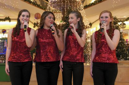 Members of Maryland Sings Escape, from left, Olivia Welling, Allie Tambaoan, Brooke Nixon and Madison Mowl, perform at The Shops at Kenilworth, in Towson, Dec. 18.