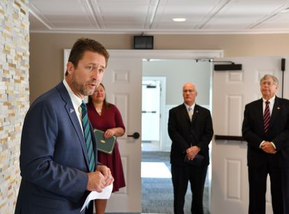 Howard K. McComas IV, left, welcomes a host of local dignitaries and others gathered for the official opening of the new Celebration of Life Center, formerly the Kurtz Funeral Home at 1114 Baldwin Mill Road.