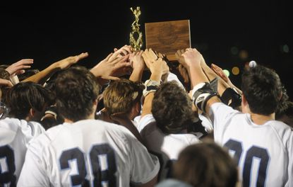 Howard players, seen here raising the championship trophy as a team after their win against Churchill during the 2015 4A/3A boys lacrosse state championship at Stevenson University's Mustang Stadium last May, are looking to capture back-to-back titles.