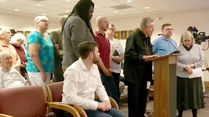 The Rev. James Snodgrass, at podium, priest-in-charge at St. John's Episcopal Church, is surrounded by church leaders and members during a June 3 Havre de Grace City Council public hearing on an ordinance revamping the city's sign code.