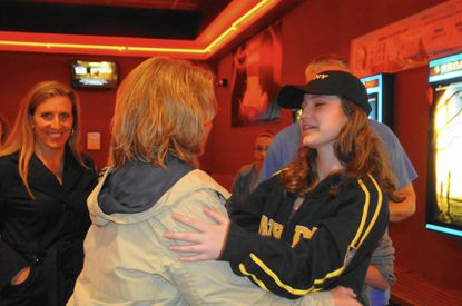 """Macey Brietenback, right, in a Sony Pictures baseball cap, greets a friend at Regal Cinema in Abingdon before a private screening of """"Miracles From Heaven"""" for New Covenant Christian School on Thursday night."""