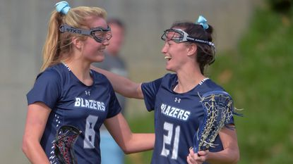Notre Dame Prep midfielder Brooke Barger (21) congratulates attacker Nancy Halleron (8) after she scored against the RPCS Reds during a key IAAM A conference matchup Tue., April 9, 2019.