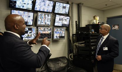 Craig Rivers, left, principal, and Karl E. Perry, Chief School Supports Officer for Baltimore city public schools, tour Mergenthaler Vocational-Technical high school this afternoon. Here, they look at a bank of security cameras which monitor all parts of the school.