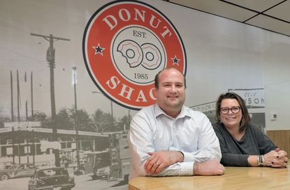 (LtoR) - Prior to their Grand Re-Opening on February 29, Donut Shack's new managing partner Ben Hilliard and owner/operator Ali Matthews relax at a counter visited by Severna Park families for more than three decades. They've kept the shop as it was when owned by Bill and Stacey Prevezanos but enhanced its retro feel with the addition of a wall-sized photo of downtown Severna Park circa the mid 1950's. Photo by Sharon Lee Tegler, Correspondent