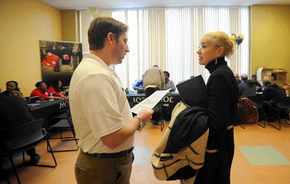 Noah Hirsch, left, the vice president of marketing for Horseshoe Casino Baltimore, talks with Carol Clark, of Homeland, during a casino job fair in Govans on March 15.