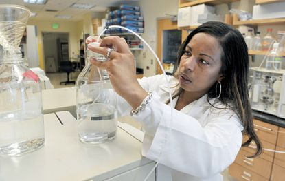 Antonia Tolson uses a solution of methanol and water to flush a machine. She has a grant to finish her research at the University of Maryland School of Pharmacy on the interaction between methadone and drugs to treat illnesses such as HIV and hepatitis C.