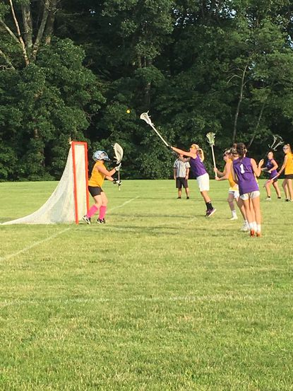 Sarah Streett of Purple reaches for the ball with Gold goalie Liz Palmer set to defend.