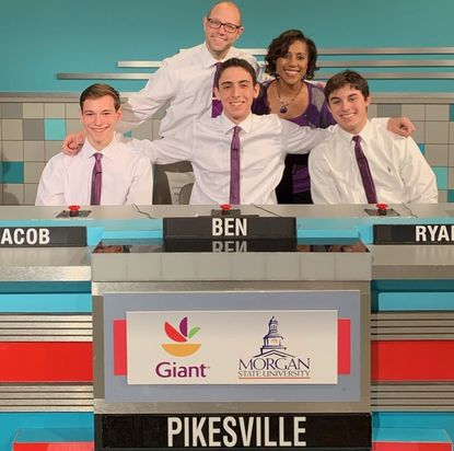 """Pikesville High School """"It's Academic"""" Coach Ethan Goodman and former Principal Sandra Reid (top row) pose with team members (bottom row, left to right) Jacob Lane, Ben Matz and Ryan Kornblit in this 2020 photo."""