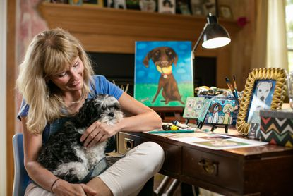Cheri Glover of Columbia holds her dog, Gracie, an 8-year-old Shih Tzu-poodle mix, at her home studio. She's one of several local artists who've tapped into the demand for pet portraits.