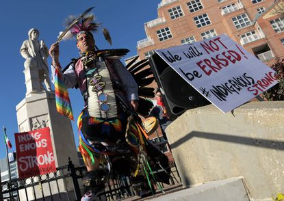 Andrew Thompson of the Choctaw Nation of Oklahoma brings his dance down the steps at the statue of Christopher Columbus at a rally for Indigenous Peoples' Day Fri., Nov. 29, 2019. (Karl Merton Ferron/Baltimore Sun Staff)