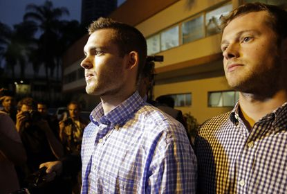 American Olympic swimmers Gunnar Bentz, left, and Jack Conger leave a police station in the Leblon neighborhood of Rio de Janeiro, Brazil, Thursday, Aug. 18, 2016. The two were taken off their flight from Brazil to the U.S. on Wednesday by local authorities amid an investigation into a reported robbery targeting Ryan Lochte and his teammates. A Brazilian police officer told The Associated Press that Lochte fabricated a story about being robbed at gunpoint in Rio de Janeiro.