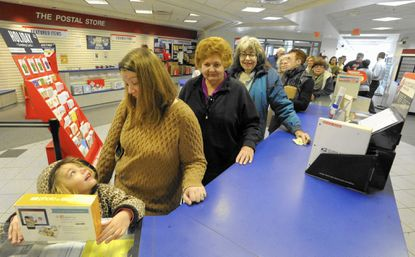 Piper Gawel, 5, and her mother Jennifer wait in the long line at the Westminster Post Office on Monday.