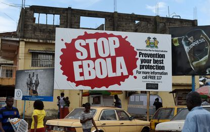 People walk past a billboard with a message about ebola in Freetown.