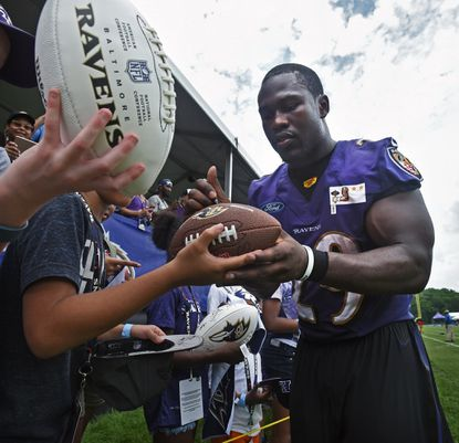 Ravens running back Justin Forsett signs autographs for fans after finishing first day of training camp for the 2016 season.