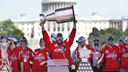 In this June 12, 2018, file photo, Washington Capitals' Alex Ovechkin, of Russia, holds up the Stanley Cup trophy during the NHL hockey team's Stanley Cup victory celebration at the National Mall in Washington. The U.S. Capitol rises in the background.