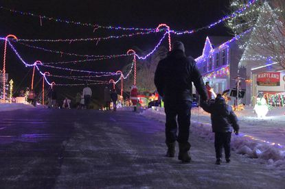 Visitors walk under the lights on McCurley Drive in Carroll County, a street with no outlet that has become a holiday destination.