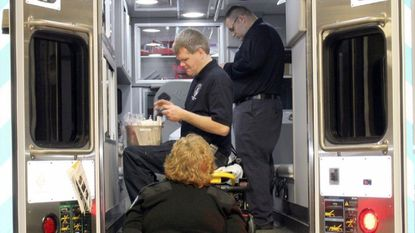 Harford County paramedics Justin Wolfe, front, and Chris Smith, rear, check supplies on Harford County's new 'surge' ambulance while Tami Wiggins, EMS manager for the county, watches. The ambulance went into service at 7 a.m. Sunday with Smith and Wolfe on the first shift.