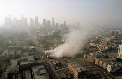 In this April 30, 1992 file photo, smoke rises from a shopping center burned by rioters in Los Angeles after four police officers had been acquitted of the 1991 beating of motorist Rodney King.