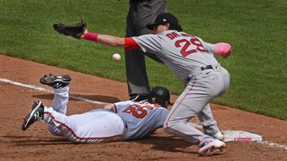 Orioles pinch runner Ryan McKenna, bottom, dives back to first base as the ball gets away from Red Sox's Bobby Dalbec, right, on a pickoff attempt in the sixth inning.