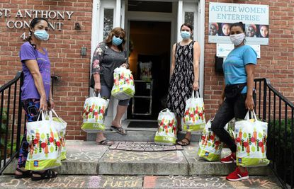 Staff members and volunteers at Asylee Women Enterprise collect food for asylum seekers and other immigrants in the city. From left: Arnobia Bernal, Lynne Cummings, Katie Kriss and Lesli Ordoñez.