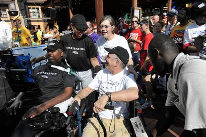 O.J. Brigance, a former Ravens player who is battling ALS, smiles as his wife, Chanda, speaks with Fred Carlson and his wife, Mary Jo, at the Fiesta 5K, a fundraiser for ALS research.