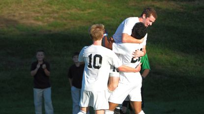 McDonogh'sLuke Davis (10), Casey Settleman, top, and Mason Christian congratulate one another after a goal against Archbishop Curley in the Eagles' 3-1 win.