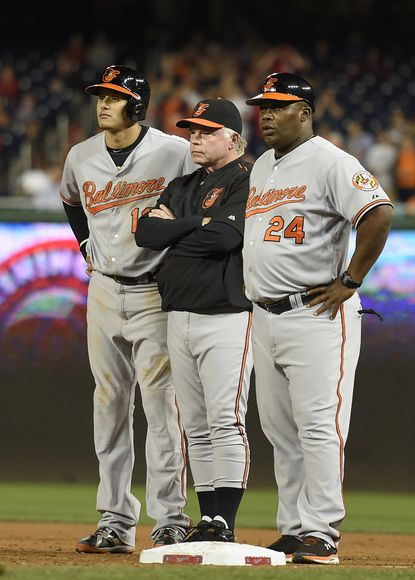 Baltimore Orioles' Manny Machado, left, stands at first base next to manager Buck Showalter, center, and first base coach Wayne Kirby (24) during the ninth inning of an interleague baseball game after Machado was hit by a pitch by Washington Nationals relief pitcher Jonathan Papelbon, not seen, Wednesday, Sept. 23, 2015, in Washington. The Orioles won 4-3.
