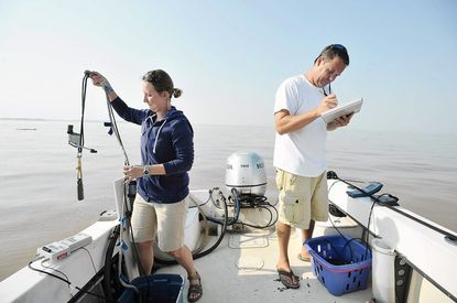 DNR biologists Zofia Noe and Jamie Strong stop off Rock Hall to record data from water monitoring devices. Noe is holding a device that measures light attenuation. They are sampling five sections of the Chesapeake Bay.