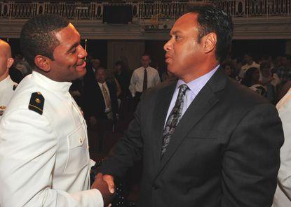 Former Navy defensive lineman Jabaree Tuani, left, shakes hands with coach Ken Niumatalolo at graduation Friday in Annapolis.