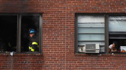 A resident of Perkins Homes peers out her window as Baltimore firefighters finish off a fire next door.
