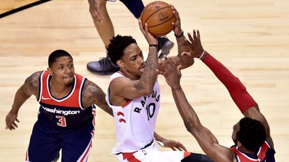 Raptors guard DeMar DeRozan drives as Wizards guards John Wall, right, and Bradley Beal defend during the second half of Game 2 of an Eastern Conference first-round playoff series Tuesday in Toronto.