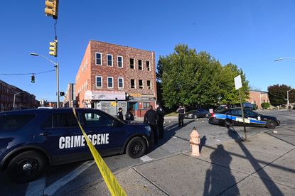 Baltimore Police Department officers investigate a crime scene at Laurens and N. Carey streets.