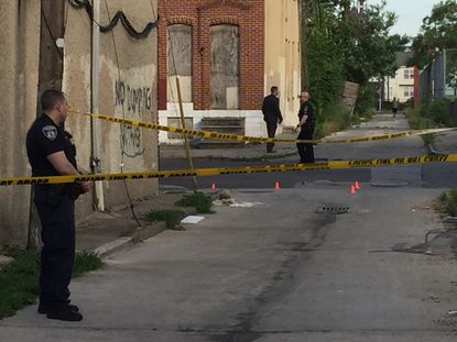 An officer stands watch over a shooting scene in West Baltimore on Friday evening.