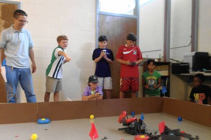 Greg Kallaur, left, looks on during a round of competition while two groups of students guide their robots at the Ridgely Robotics Camp. From left are, Malek DeBrabander, 10, of Towson, Julia Kallaur, 10, of Lutherville (seated), Archer Skeels, 11, of Lutherville, Rene DeBrabander, 12, of Towson, Alexa Silao, 11, of Lutherville, and Didier Osias, 10, of Timonium.