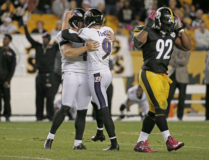 Baltimore Ravens kicker Justin Tucker (9) celebrates with holder Sam Koch (4) as Pittsburgh Steelers outside linebacker James Harrison (92) walks away after making the game winning field goal in overtime of an NFL football game against the Pittsburgh Steelers, Thursday, Oct. 1, 2015 in Pittsburgh. The Ravens won 23-20 in overtime.