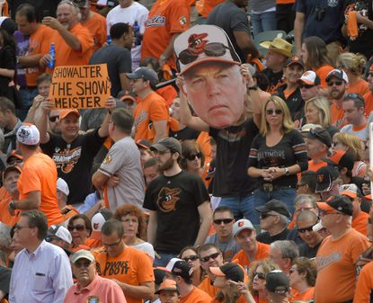 Fans hold signs including those honoring Orioles manager Buck Showalter during Game 2 of the ALDS.