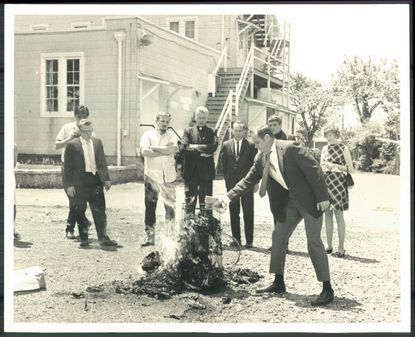 """Thomas Melville puts more fuel on a fire as Philip Berrigan and his brother, Father Daniel Berrigan, and other members of the """"Catonsville Nine,"""" watch draft records burn on May 17, 1968."""