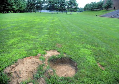 The John Carroll School has plans to install two turf fields, perhaps as early as this fall; however, a town of Bel Air sewer line runs under the fields and will most likely have to be relocated. One of the line's manholes, usually buried under a few inches of dirt, is shown.