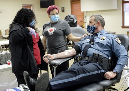 Red Cross collection tech Amya Henry, left, and charge nurse JoAnn Bell check on Carroll County Sheriff Jim DeWees as he donates blood Wednesday in the Carroll County Law Enforcement Blood Drive at the Reese fire company Social Hall March 31, 2021. More than 30 police personnel from the Carroll County Sheriff's Office, Maryland State Police, Westminster Police Department, Sykesville Police Department and Hampstead Police Department participated in the blood drive.