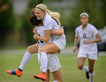 McDonogh's Bridgette Andrzejewski leaps into the arms of teammate Kasey Gibbon after scoring a goal against Good Counsel.