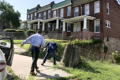 Detectives duck under the crime scene tape to investigate a fatal shooting Monday morning in the alley behind the 1000 block of Ellicott Driveway, between Lyttleton Road and Mosher Street.